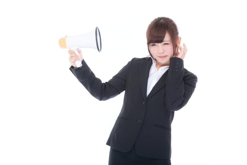 メガホンの音に耳をふさぐ女性