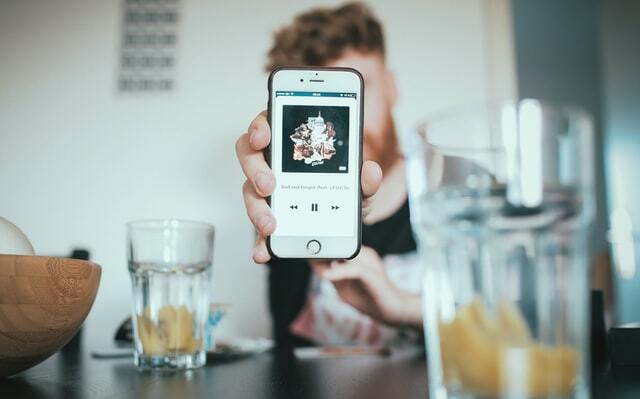 iPhoneの画面を見せる人間